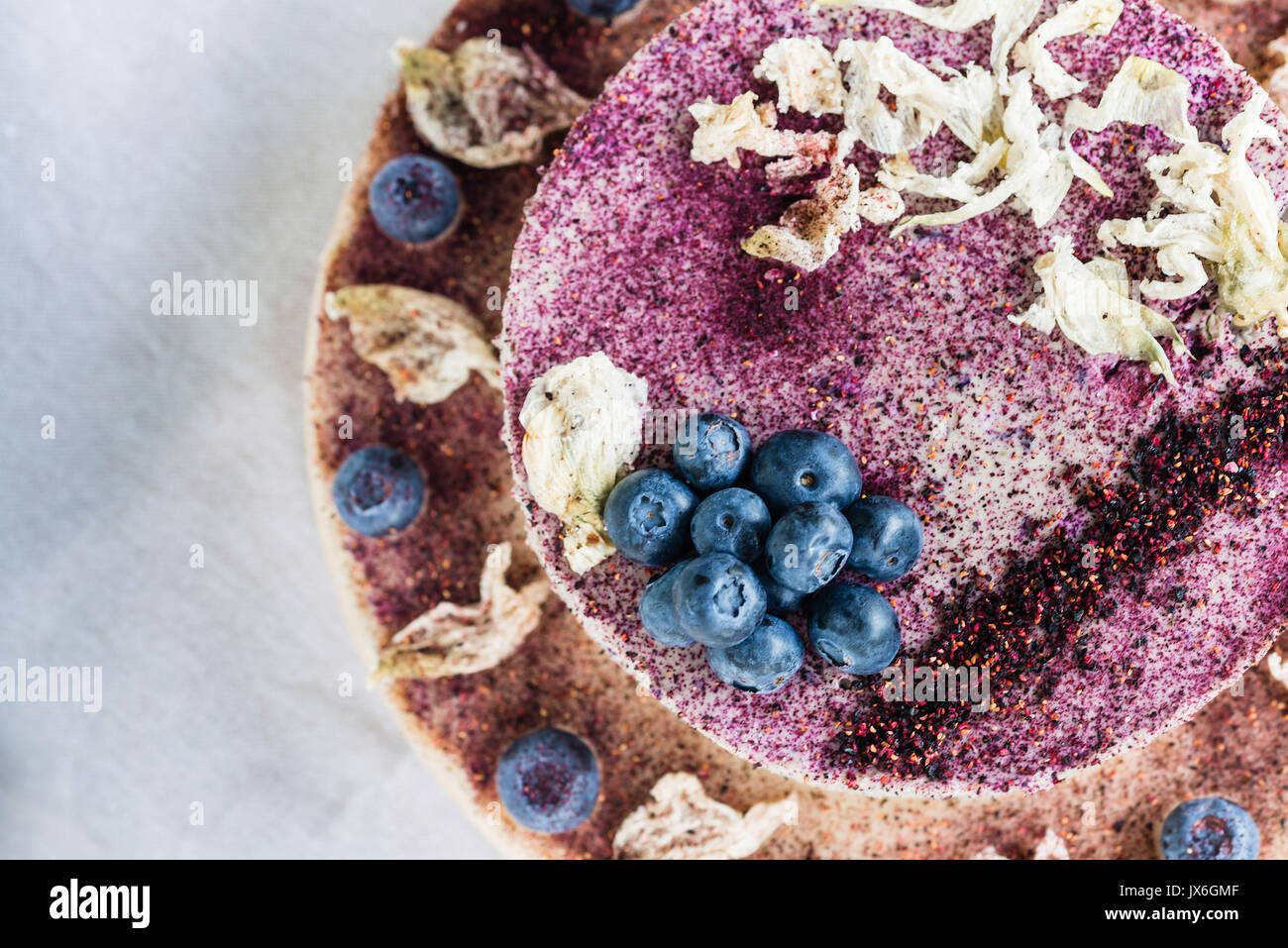 Raw blueberry cheesecake, homemade with decoration of dried flowers and fresh berries. Healthy handmade dessert. White background - Stock Image