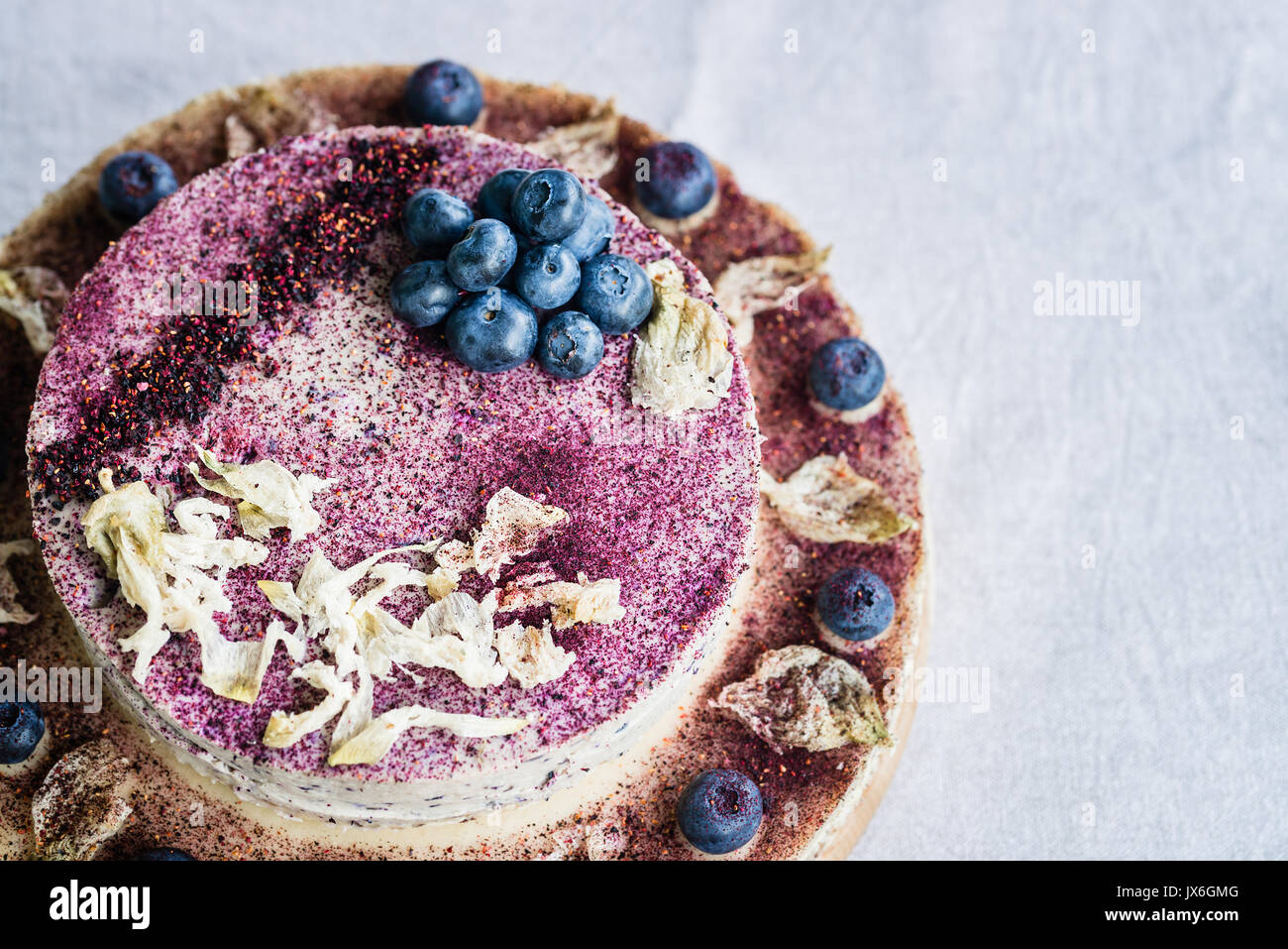 Raw blueberry cheesecake, homemade with decoration of dried flowers and fresh berries. Healthy handmade dessert. Stock Photo