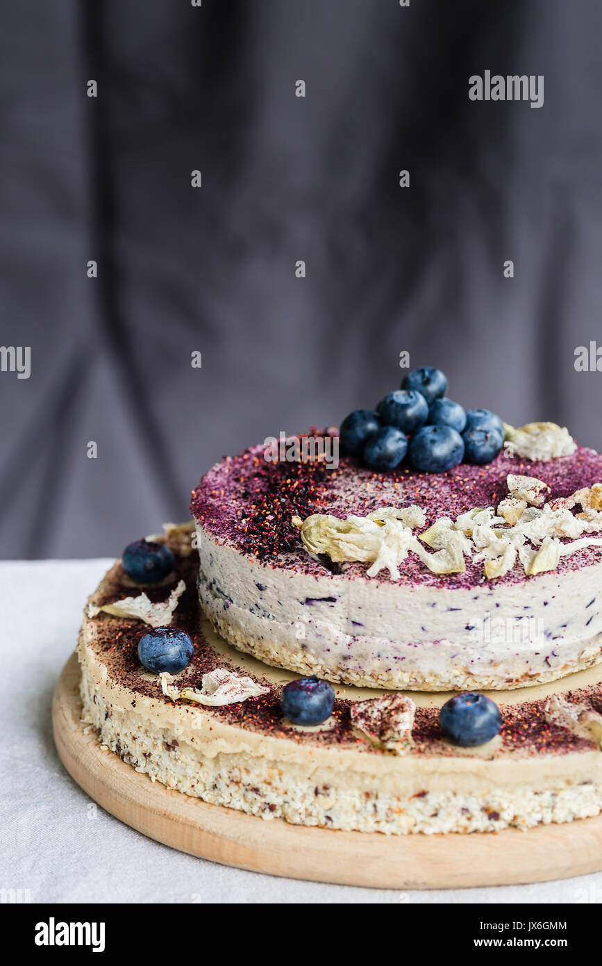 Raw blueberry cheesecake, homemade with decoration of dried flowers and fresh berries. Healthy handmade dessert. White and dark background - Stock Image