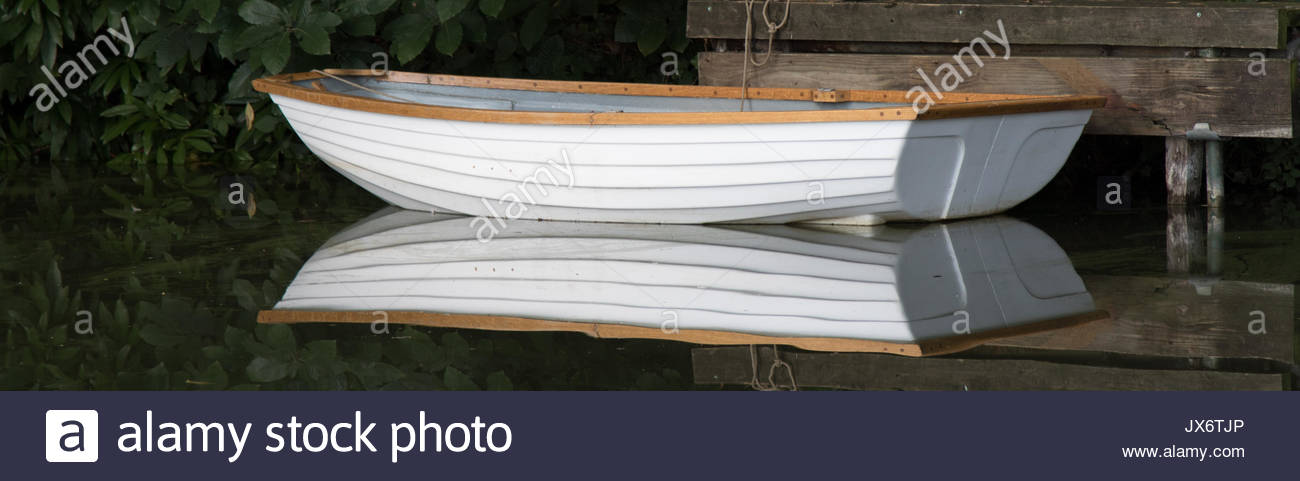 A fibreglass dinghy moored at a canal-side landing stage is reflected in the mirror-like  water of the Basingstoke canal. - Stock Image