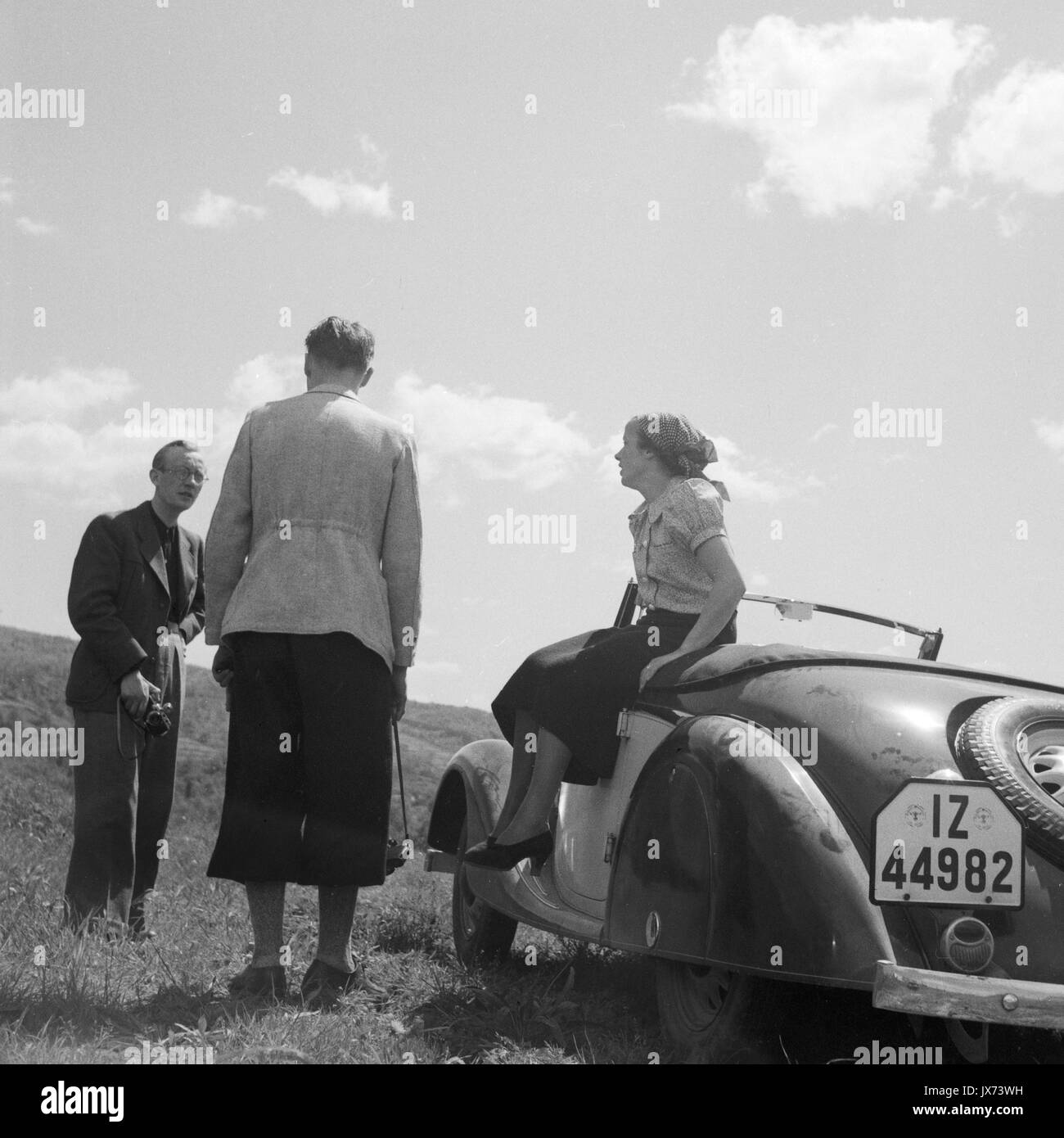 Three people talking beside car parked on grassy hill. - Stock Image