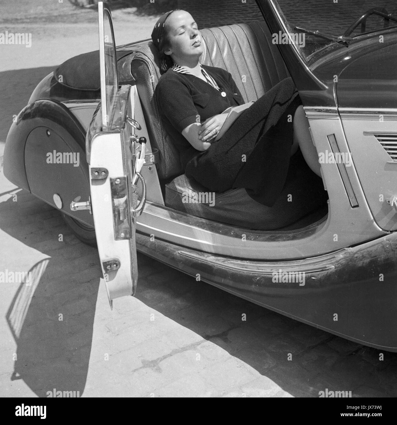 Woman resting in convertible parked outdoors. - Stock Image