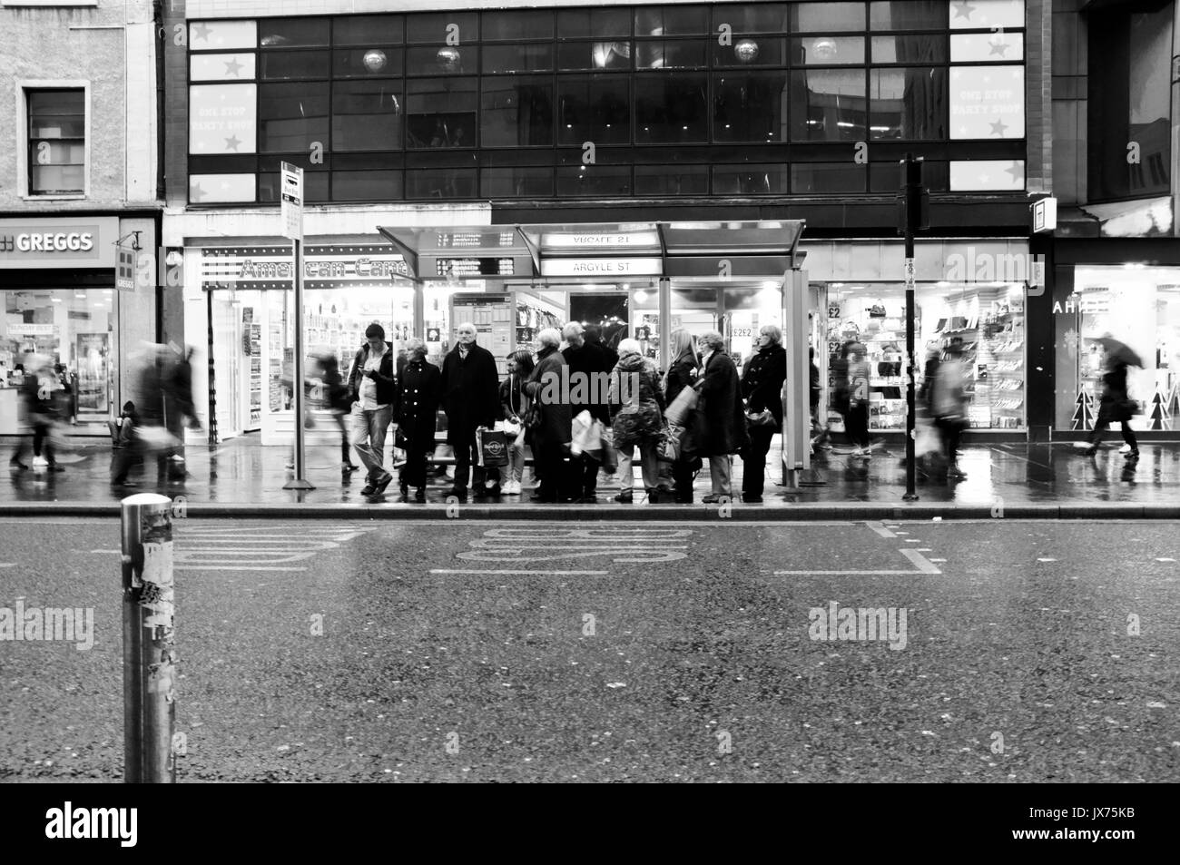 People waiting at bus stop in central Glasgow. - Stock Image