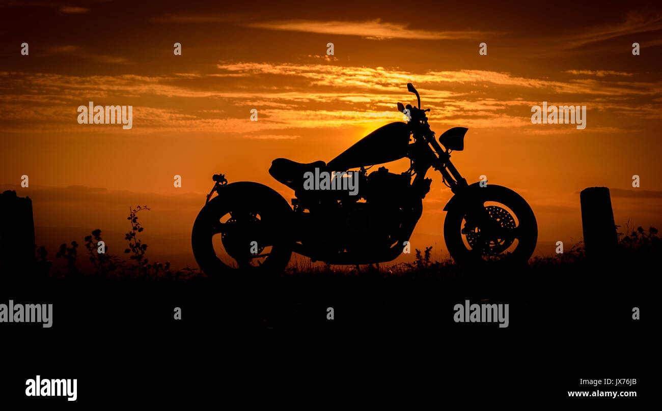 A silhouette of a custom made motorbike (chopper) against a colourful sunset, England, UK - Stock Image