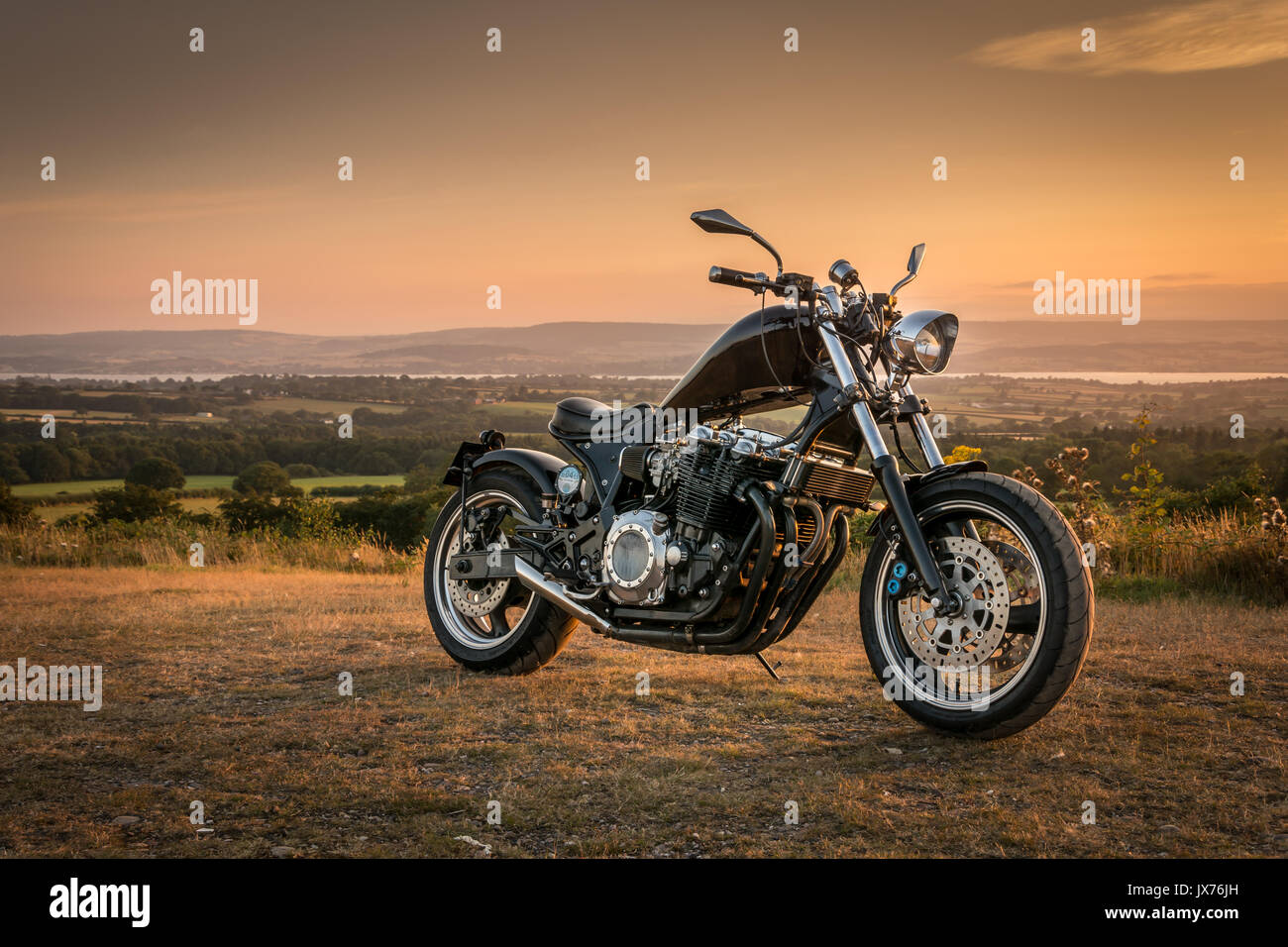 Custom made motorcycle parked during a quiet summer evening sunset. - Stock Image