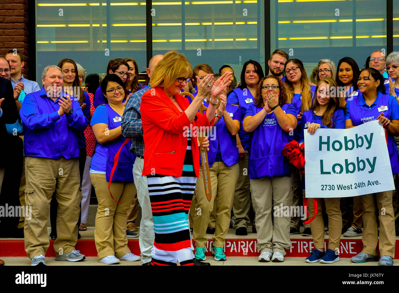 Debora Kinsey a corporate representive of Hobby Lobby  claps her hands as the ribbon is cut to signify that the newest store is now open today in Emporia, Kansas August 13. 2017. - Stock Image