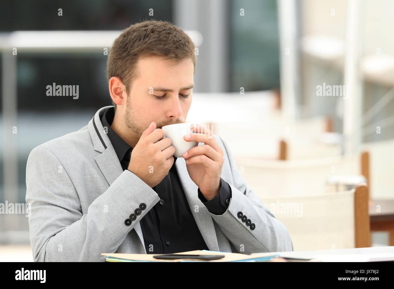 Executive drinking enjoying coffee break sitting in a bar - Stock Image