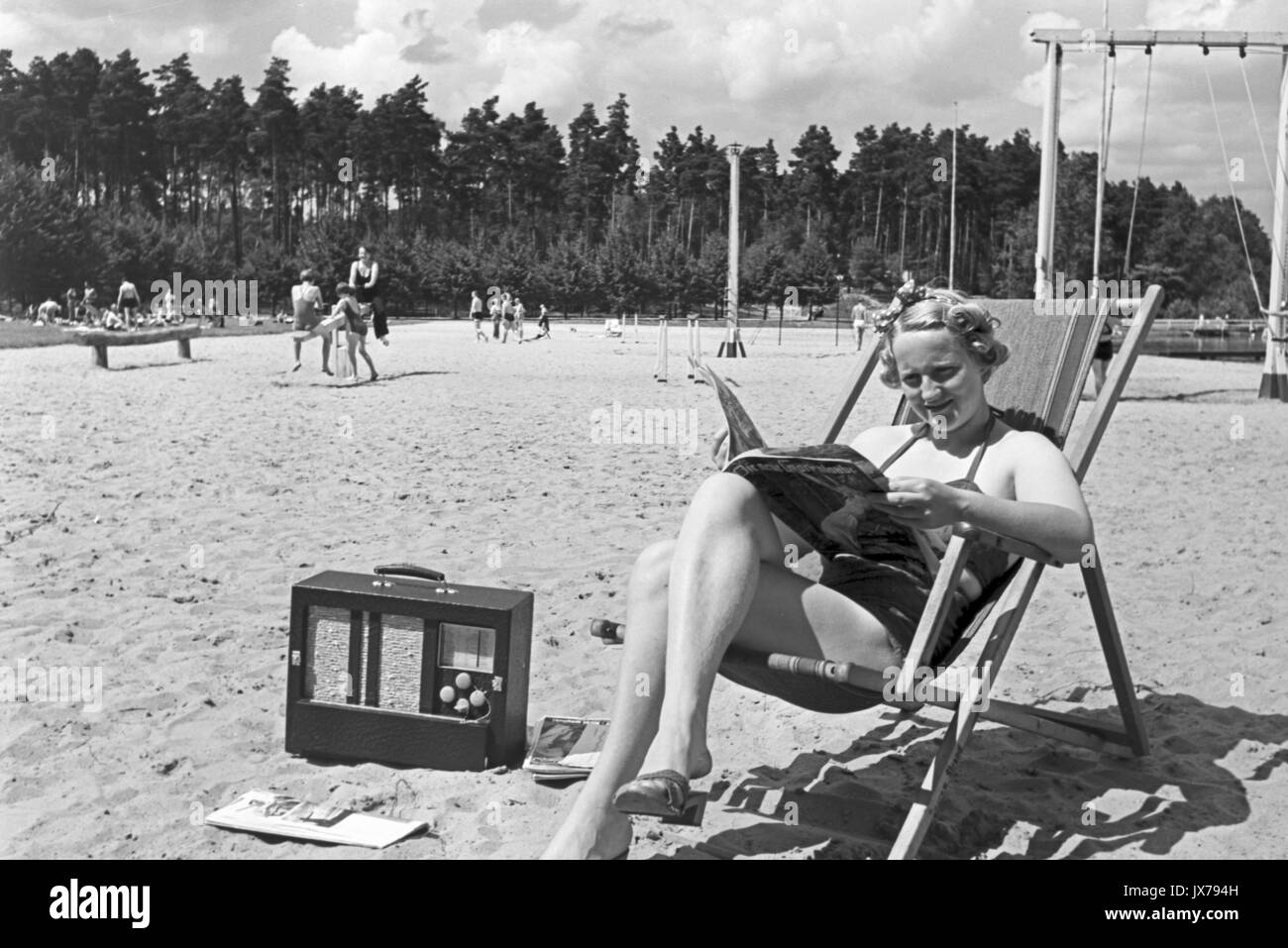 Woman reading newspaper and listening to radio on beach. - Stock Image