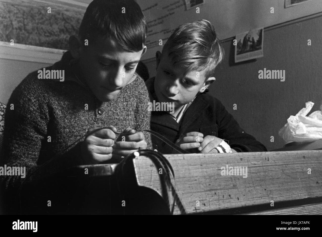 Schoolboys looking at old celluloid filmstrip in classroom. Stock Photo