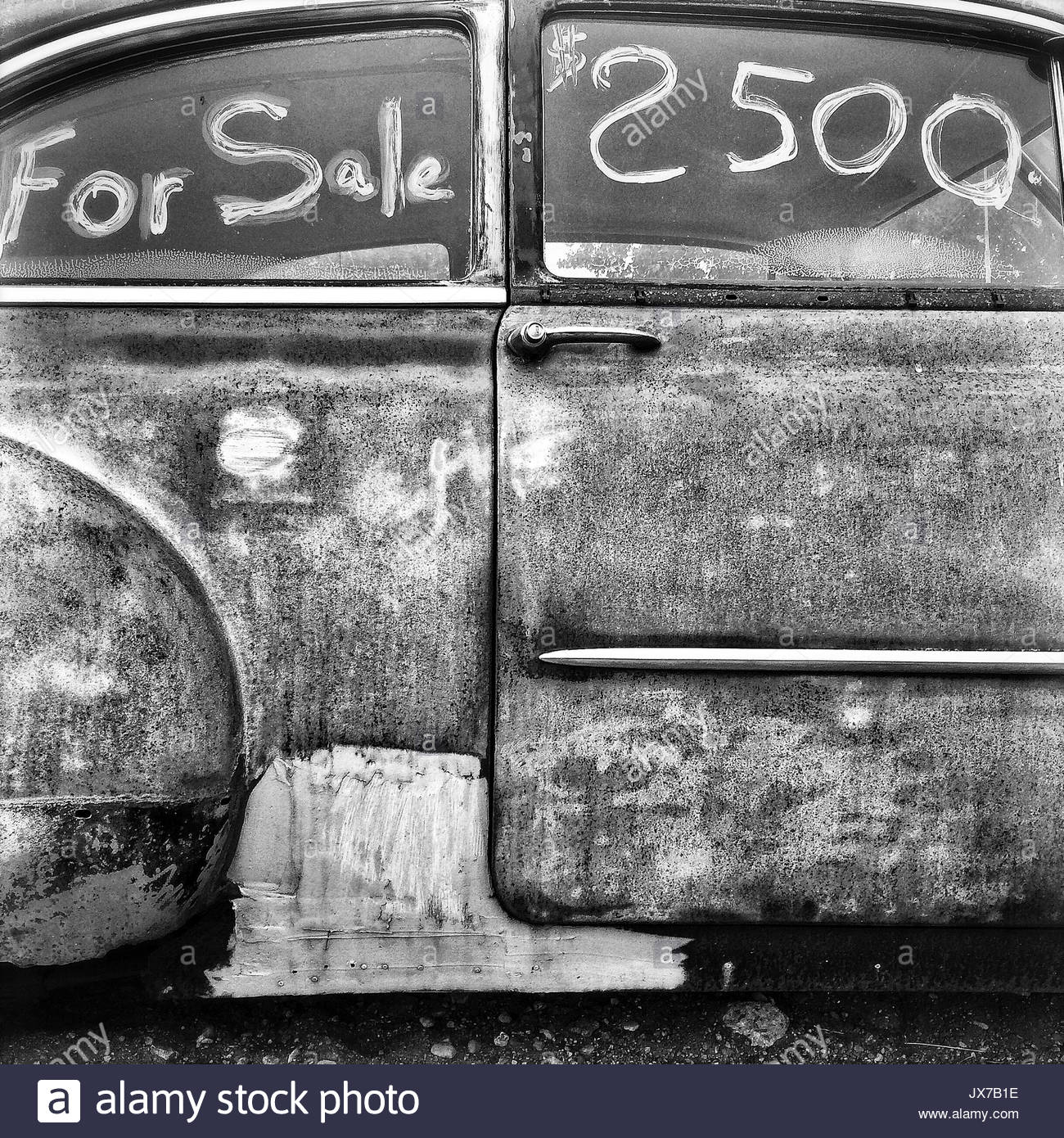 A car for sale with price written on window. - Stock Image