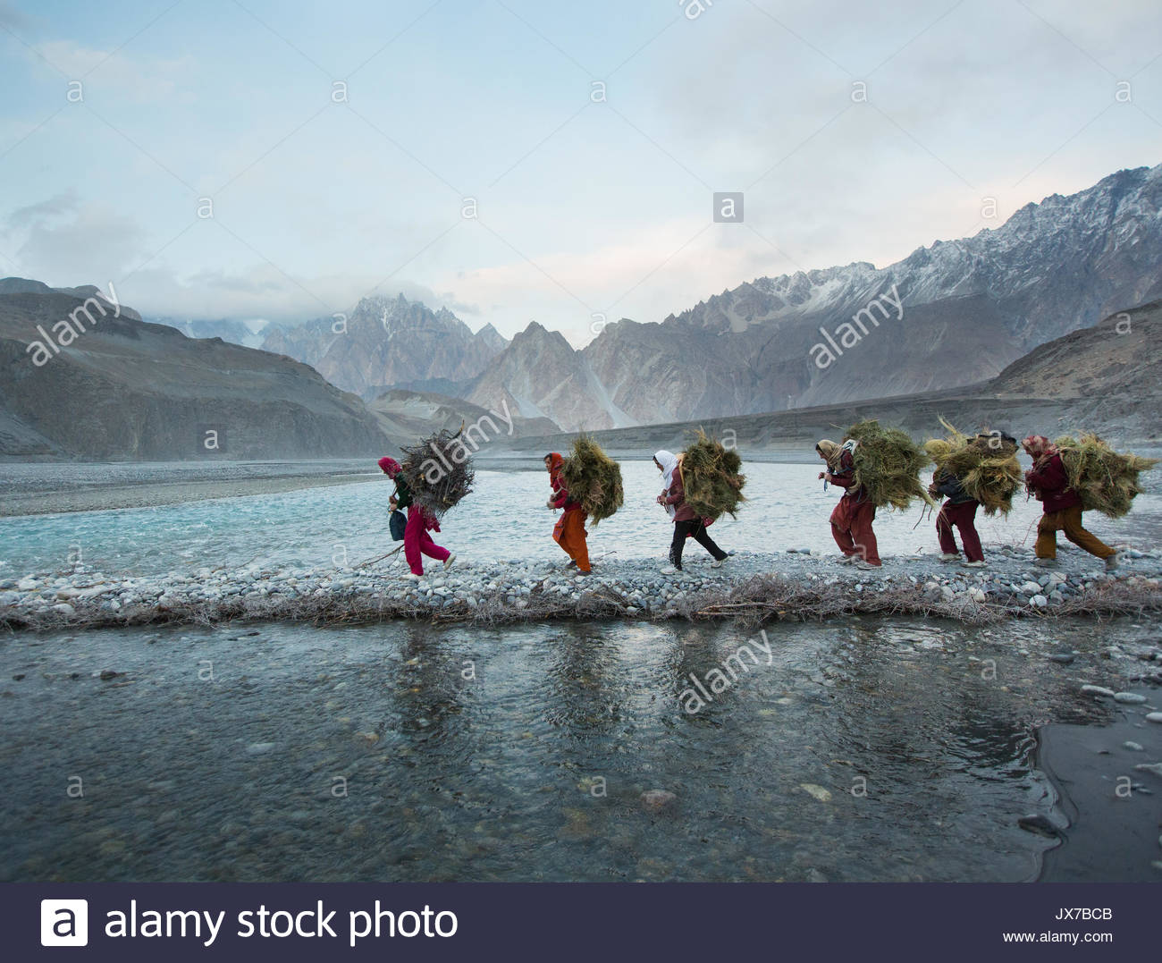 Women returning from getting wood for cooking and heating and hay to feed their livestock, a two hour walk. Stock Photo