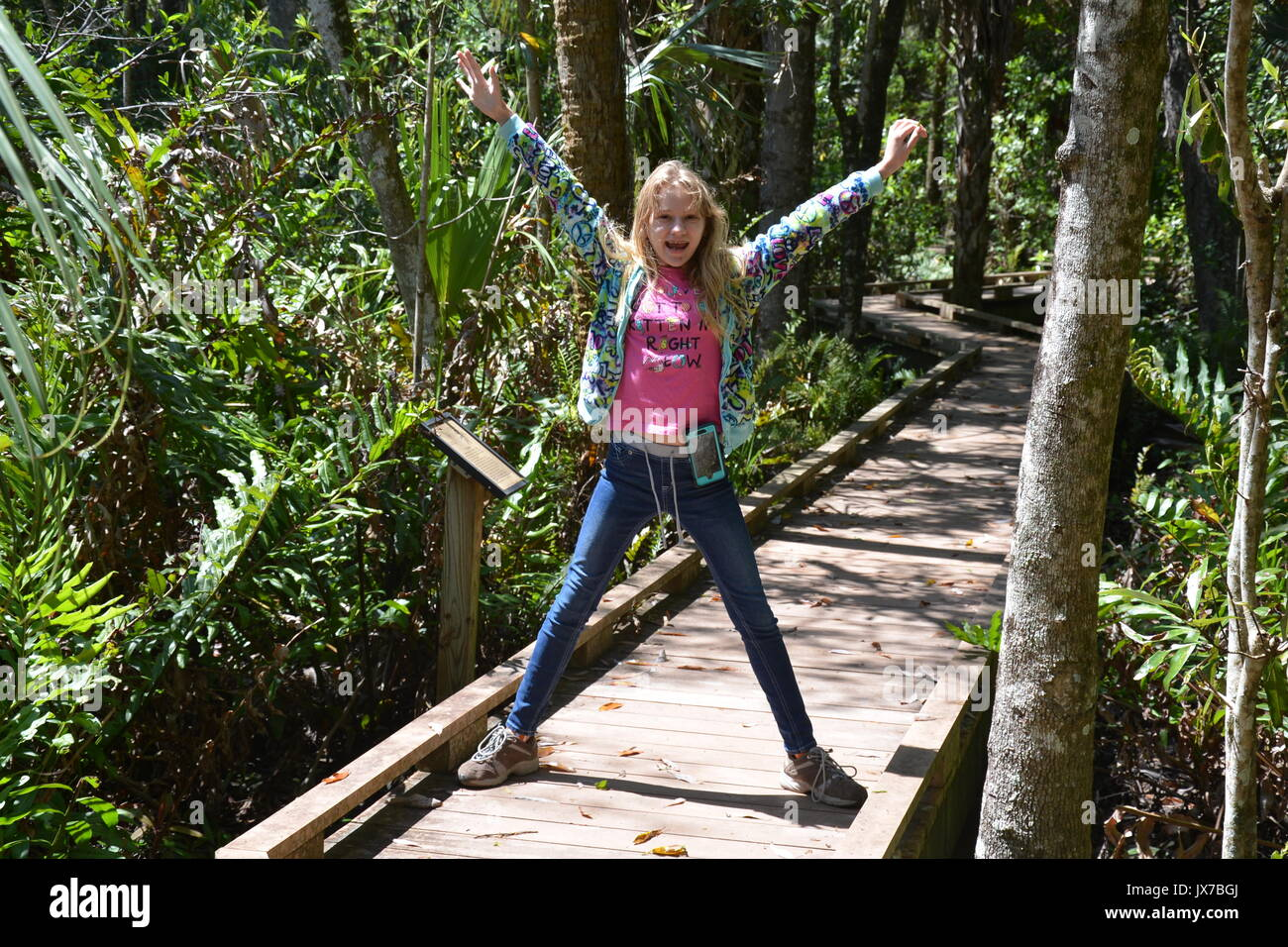 Young female acting silly on a boardwalk through the woods. Stock Photo