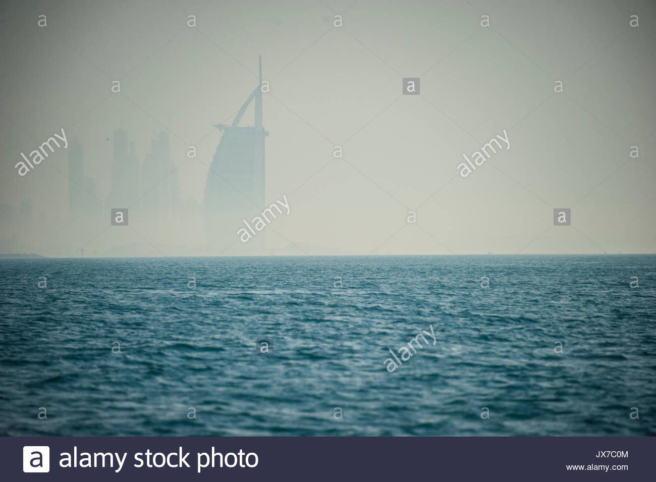 The Burj al Arab skyscraper rises off the coast of Dubai. - Stock Image