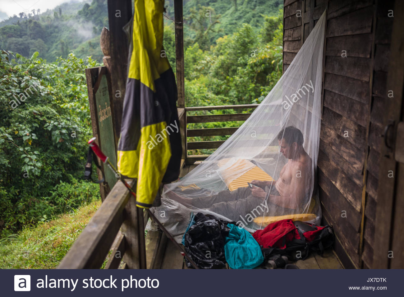 An expedition member sits outside, covered in a mosquito net, while he uses his phone. - Stock Image