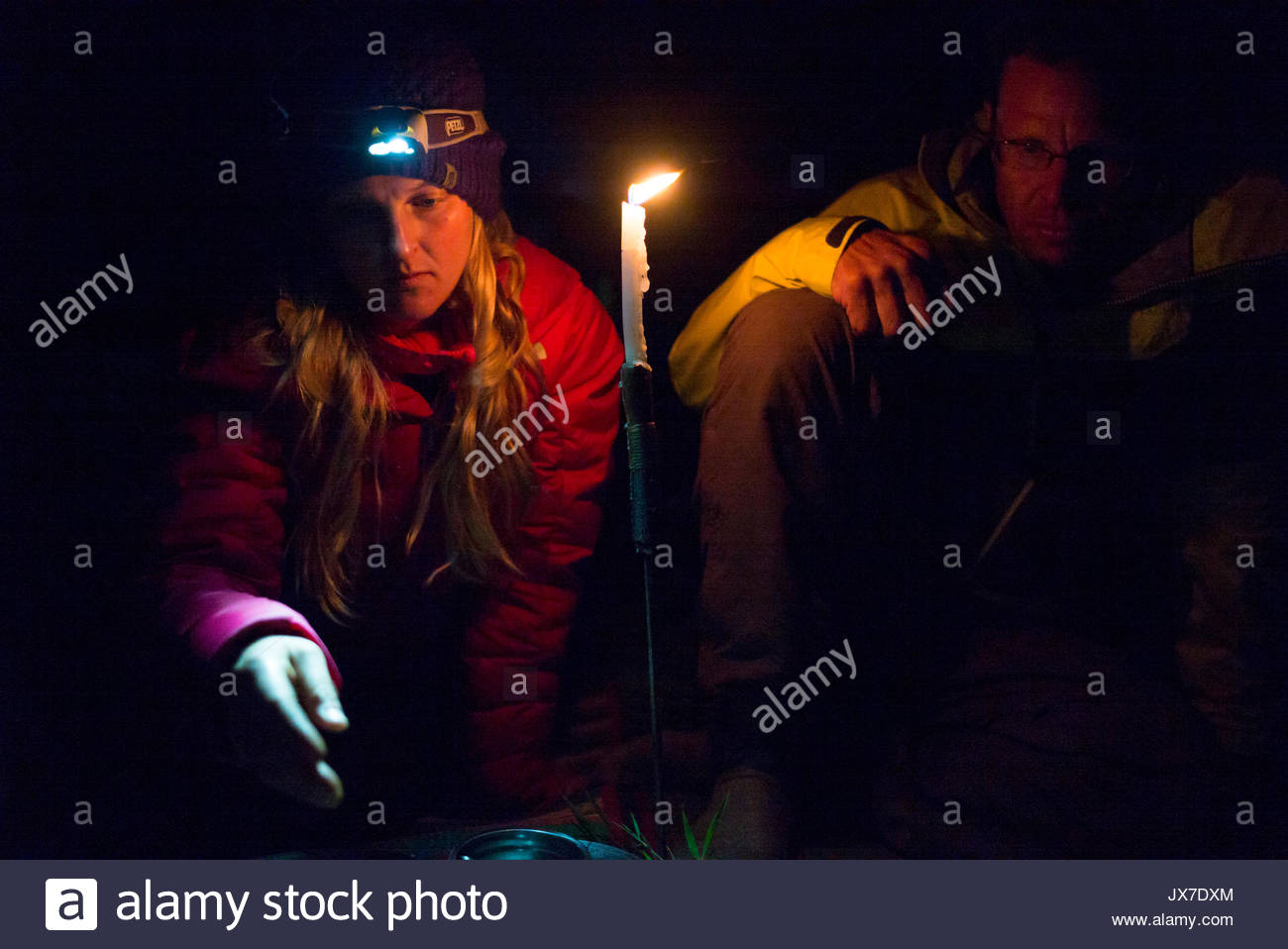 Two expedition members seated on either side of a burning candle. - Stock Image