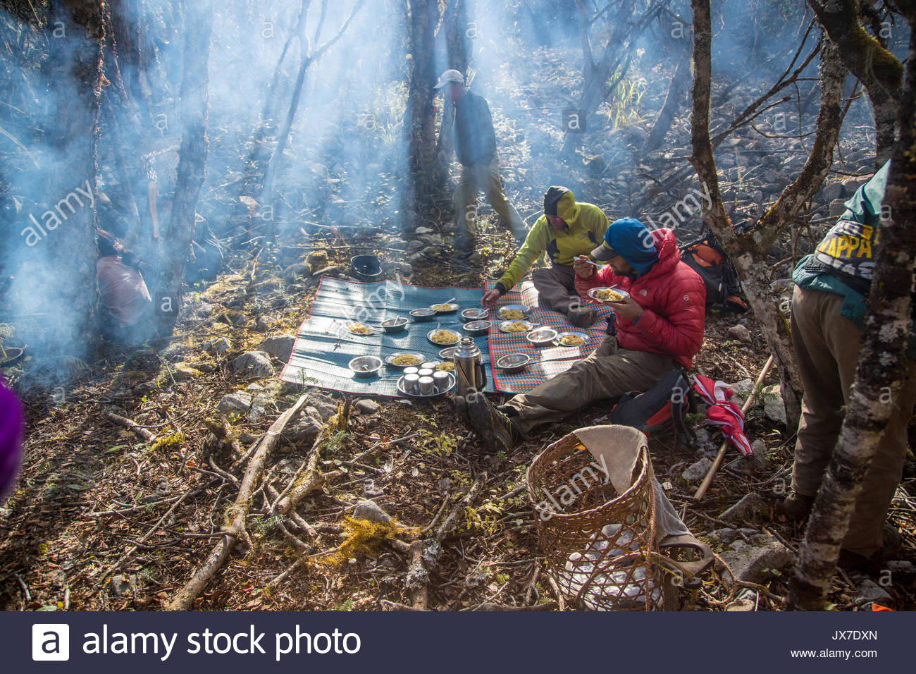 Two expedition members eat a meal while others busy themselves around the campsite. - Stock Image
