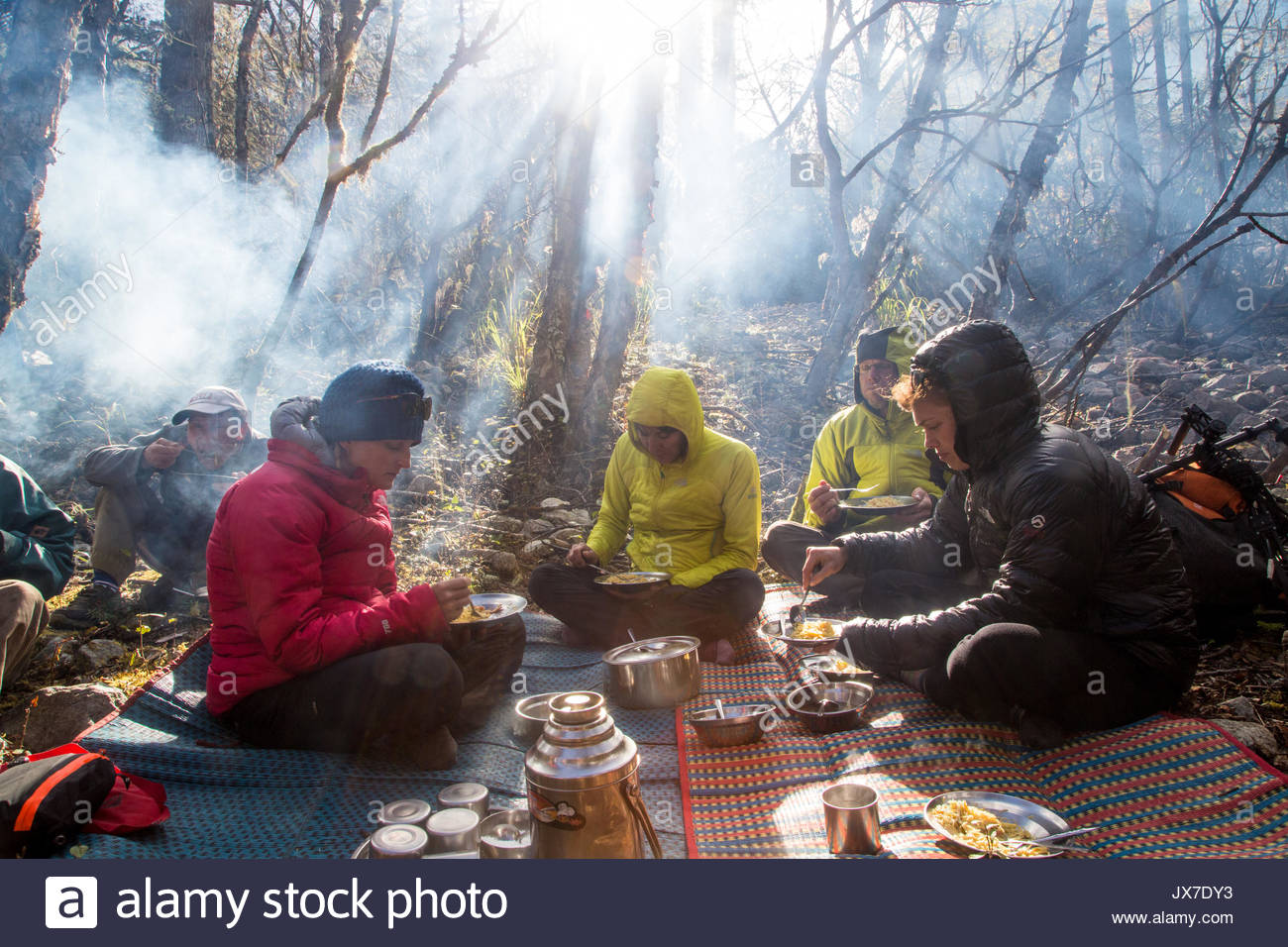 Expedition members sit around a campsite eating food. - Stock Image