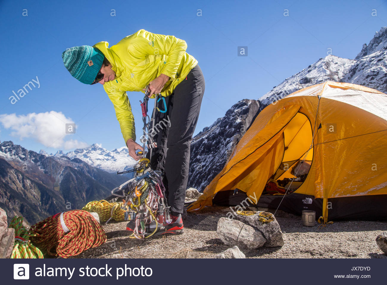 An expedition member checks carabiners, ropes and other equipment at the campsite. - Stock Image
