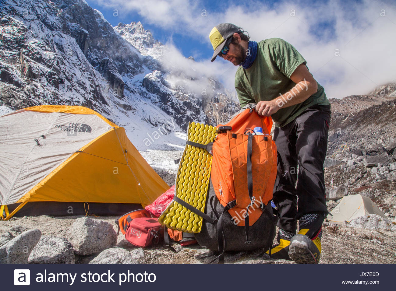 An expedition member begins to pack equipment into his backpack. - Stock Image