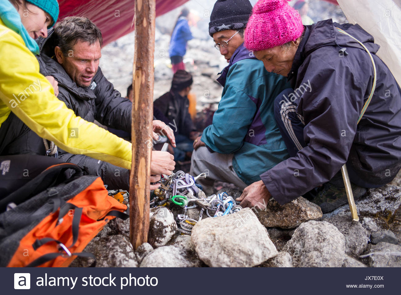 Expedition members check equipment with the help of local guides. - Stock Image