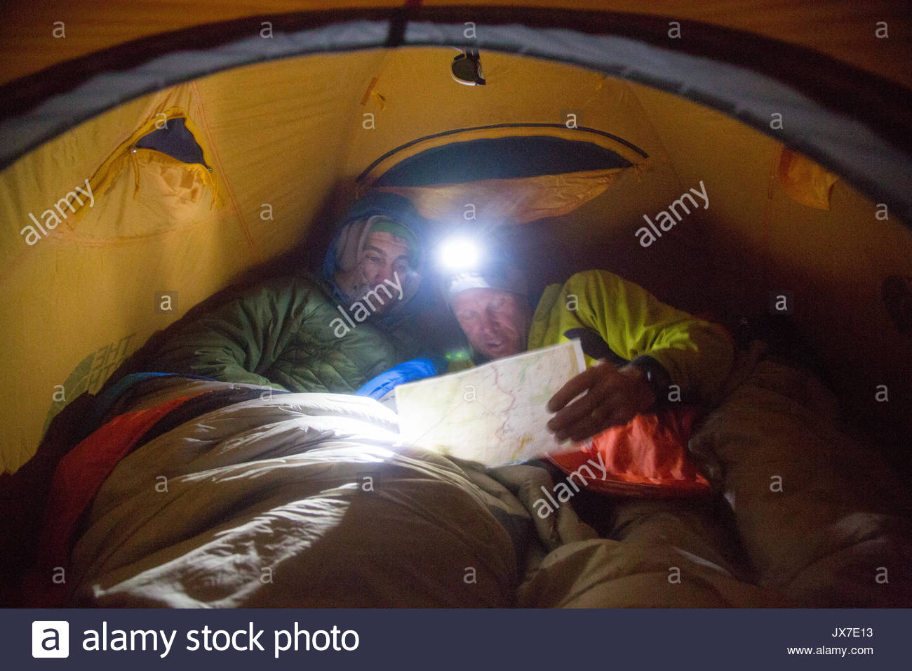 Expedition members review a map of their plans while huddled inside of a tent. - Stock Image