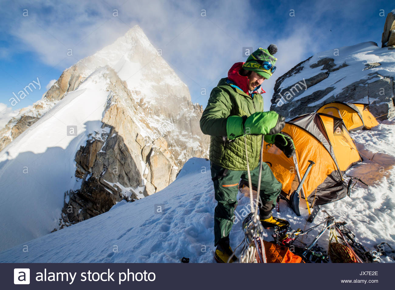 An expedition member double checks his ropes and gear. - Stock Image