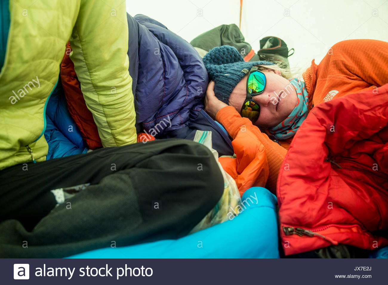 Expedition members rest and sleep inside of a tent as they attempt to summit Hkakabo Razi, said to be Southeast Asia's tallest mountain. - Stock Image
