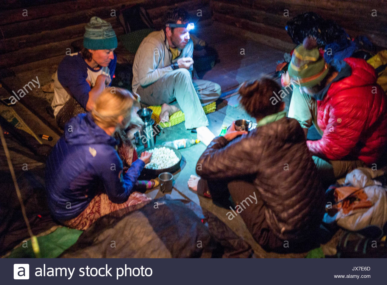 An expedition team sits together at night, eating and drinking on a mat. - Stock Image