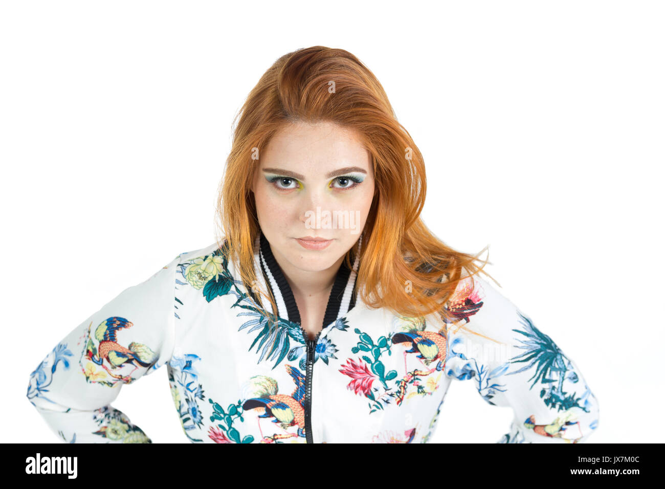Young woman looks seriously and with defiant look. Redhead girl wears a jacket with floral patterns. Summer and tropical. White background. - Stock Image