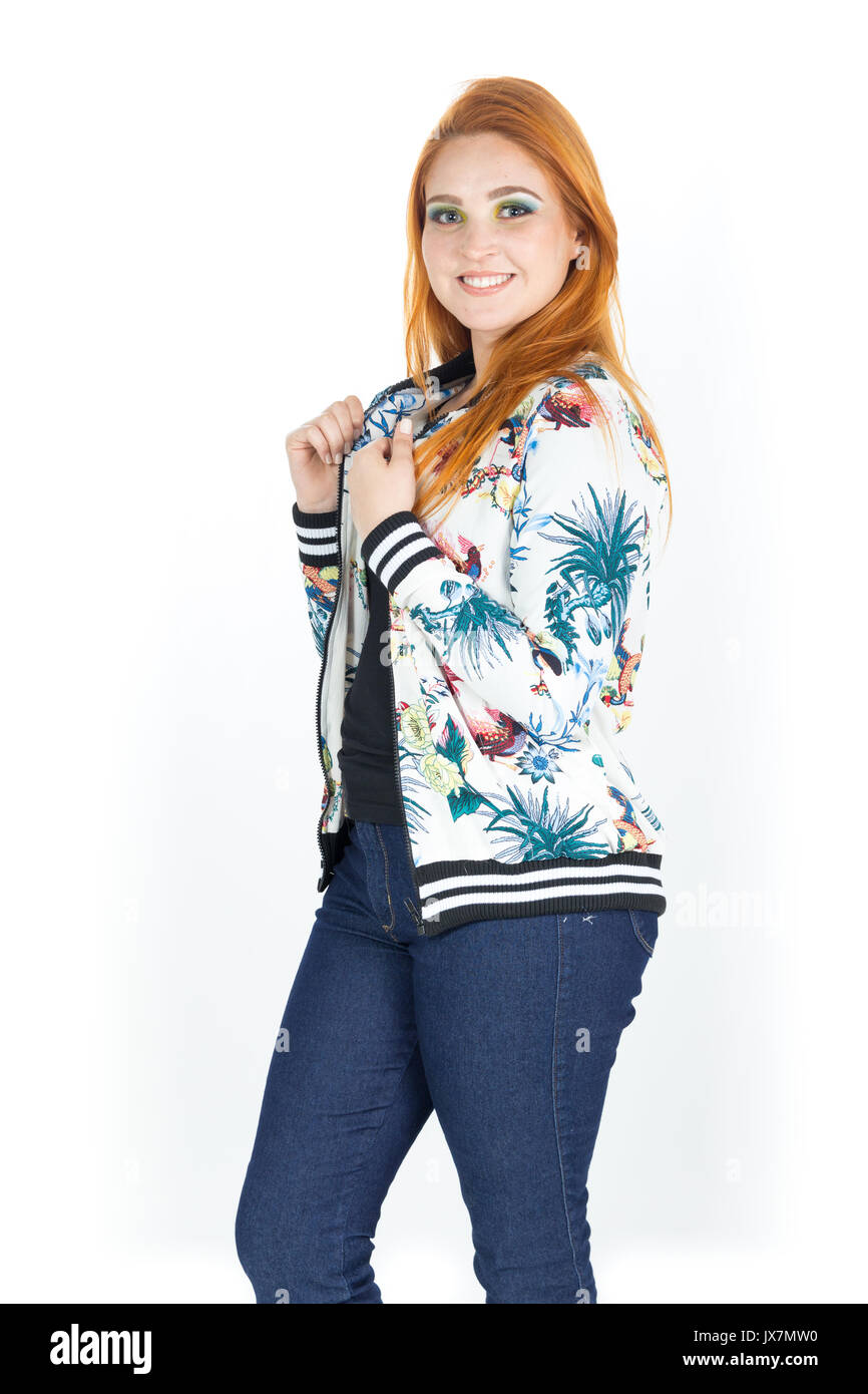 She is in profile and smiles at the camera. Redhead girl wears a jacket with floral patterns. Fashion. Style. Beauty. Summer and tropical. White backg - Stock Image
