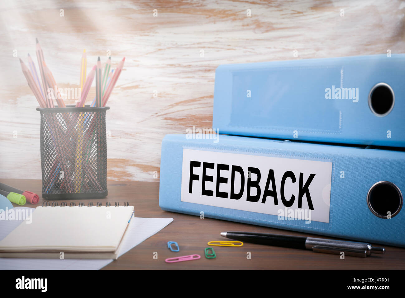 Feedback, Office Binder on Wooden Desk. On the table colored pencils, pen, notebook paper. - Stock Image