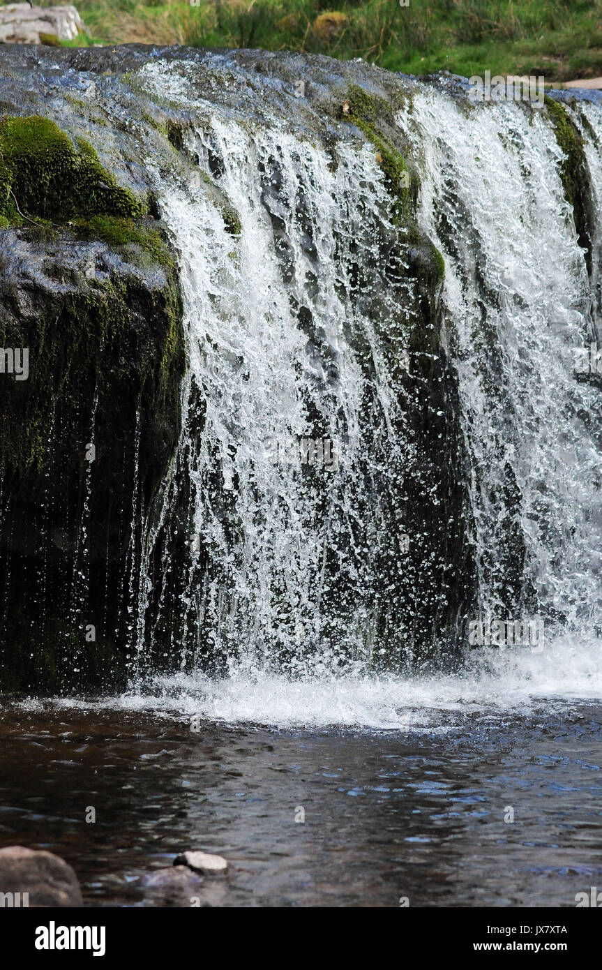 The upper of two small waterfalls on the Afon Caerfanell near its confluence with the Nant Bwrefwr. - Stock Image