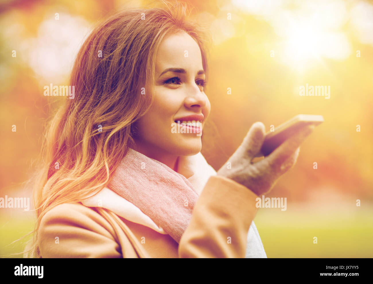 woman recording voice on smartphone in autumn park - Stock Image