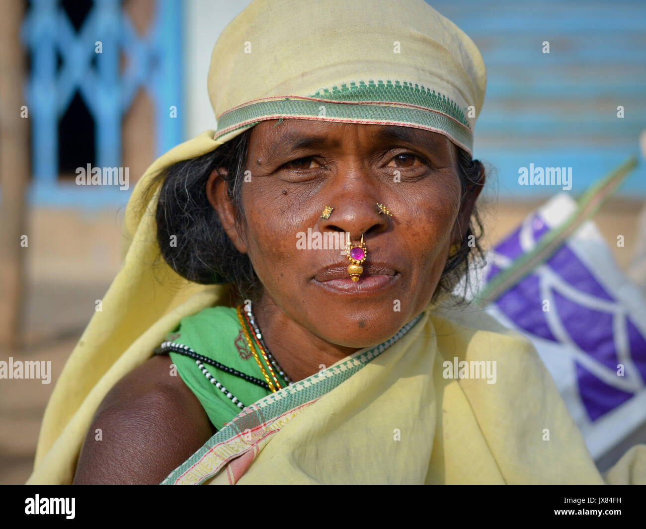 Closeup street portrait (outdoor headshot, full-face view) of a mature Indian Adivasi market woman with two nose - Stock Image