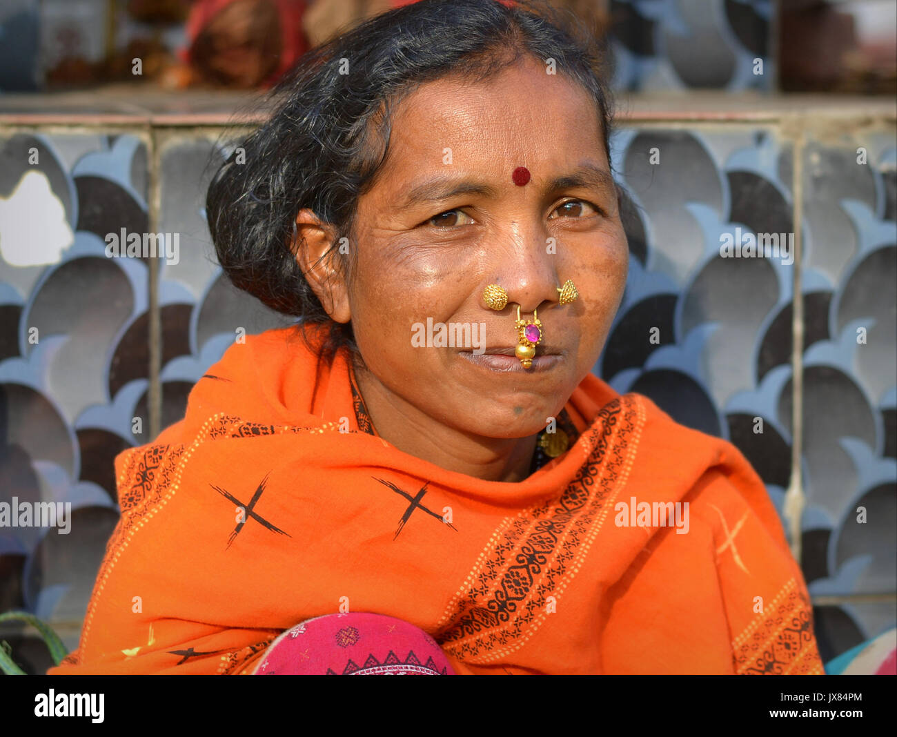 Closeup street portrait (outdoor headshot, three-quarter view) of a mature Indian Adivasi market woman with two - Stock Image