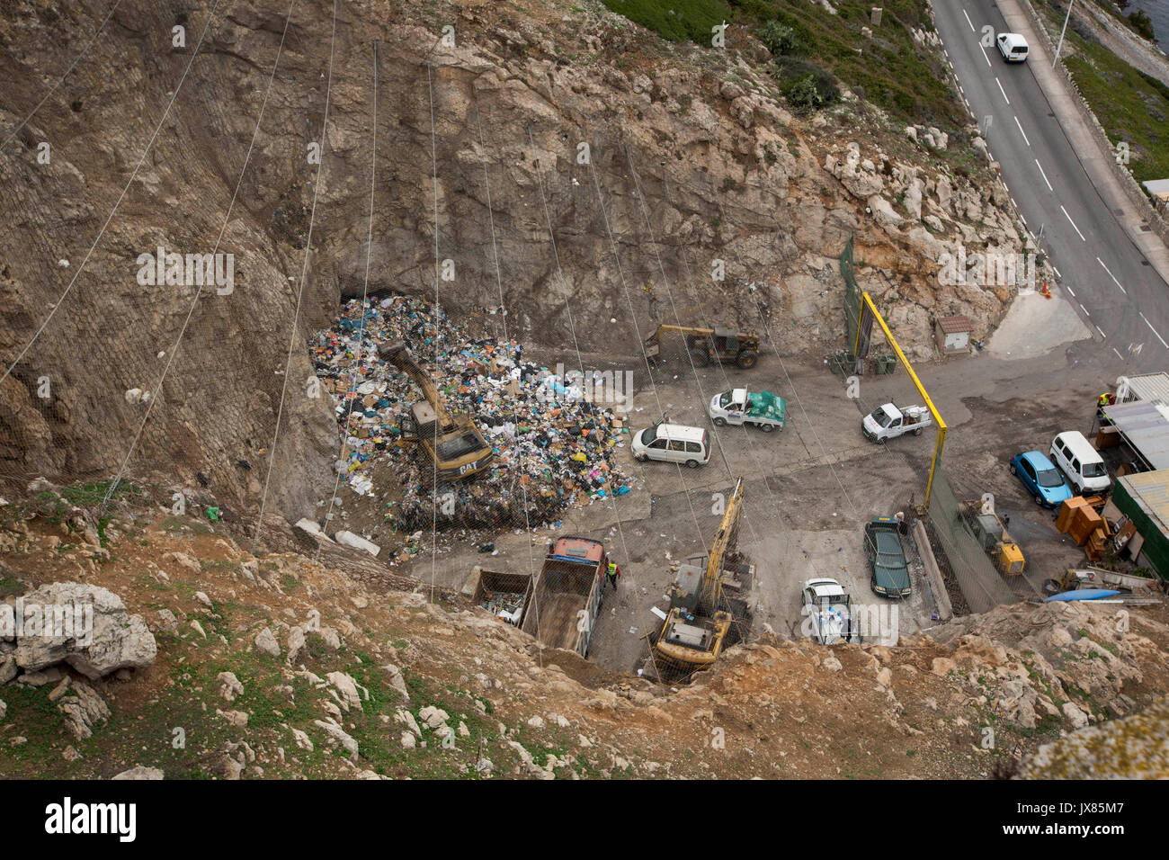 Barbary macaques scavenge for food in a busy landfill site in Gibraltar. - Stock Image