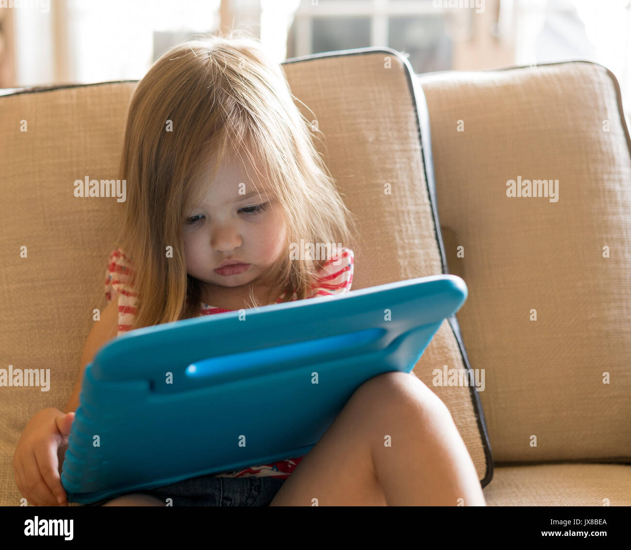 Preschool girl using a tablet computer at home - Stock Image