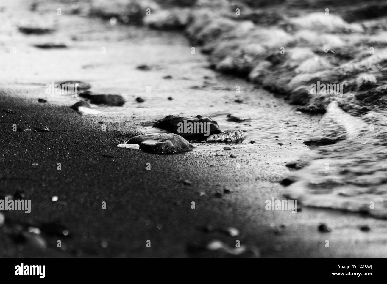 A close shot of a lake shore, with details of water bubbles and little stones and pebble on the sand - Stock Image