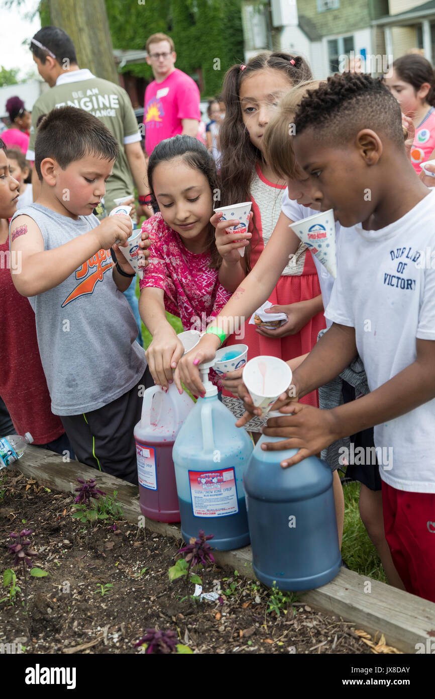 Detroit, Michigan - Children add flavored syrup to sno-kones during a summer program for kids in Clark Park. - Stock Image
