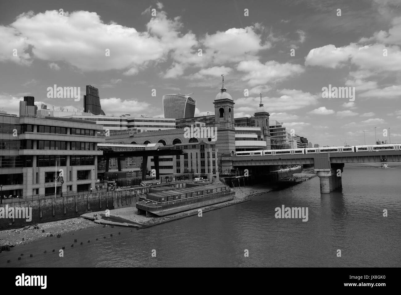 The view from Southwark Bridge showing a train leaving Cannon Street Station, the bank of the Thames and London's skyscrapers in the background. - Stock Image