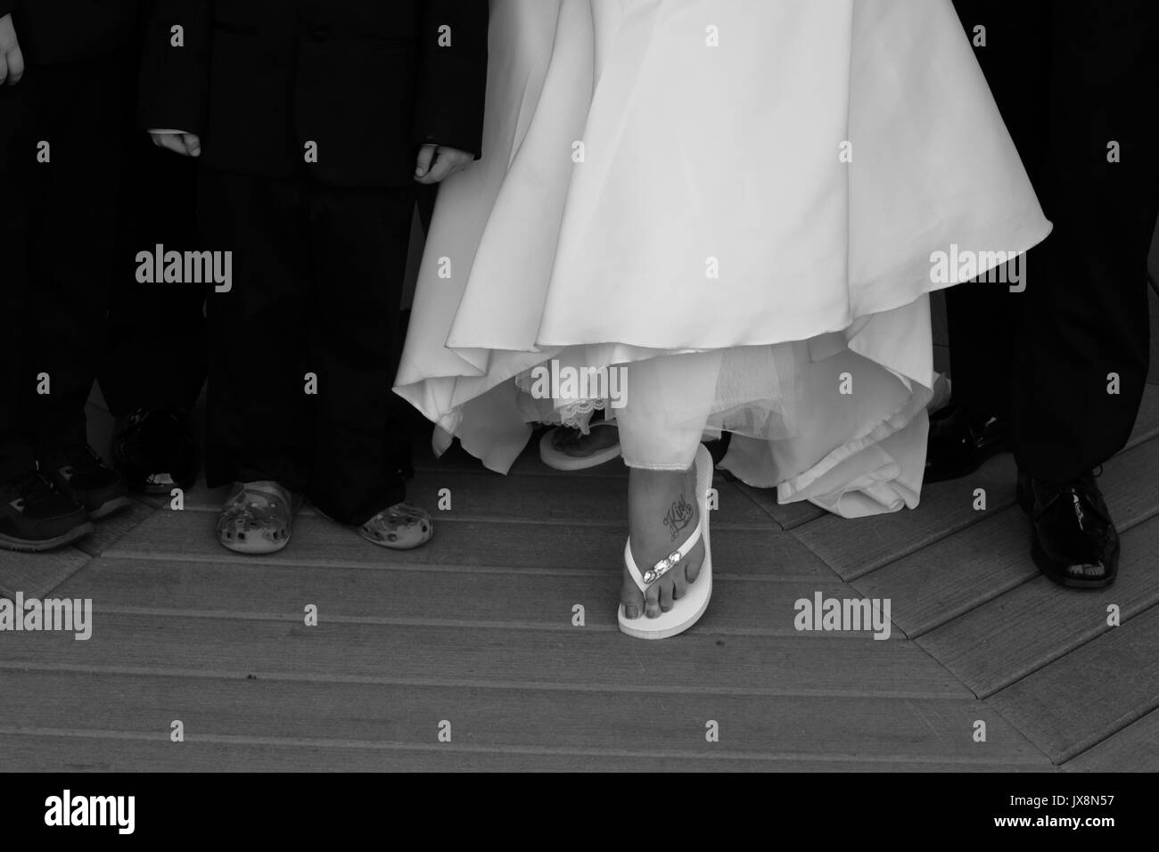 Bride shows off comfy shoes after ceremony - Stock Image