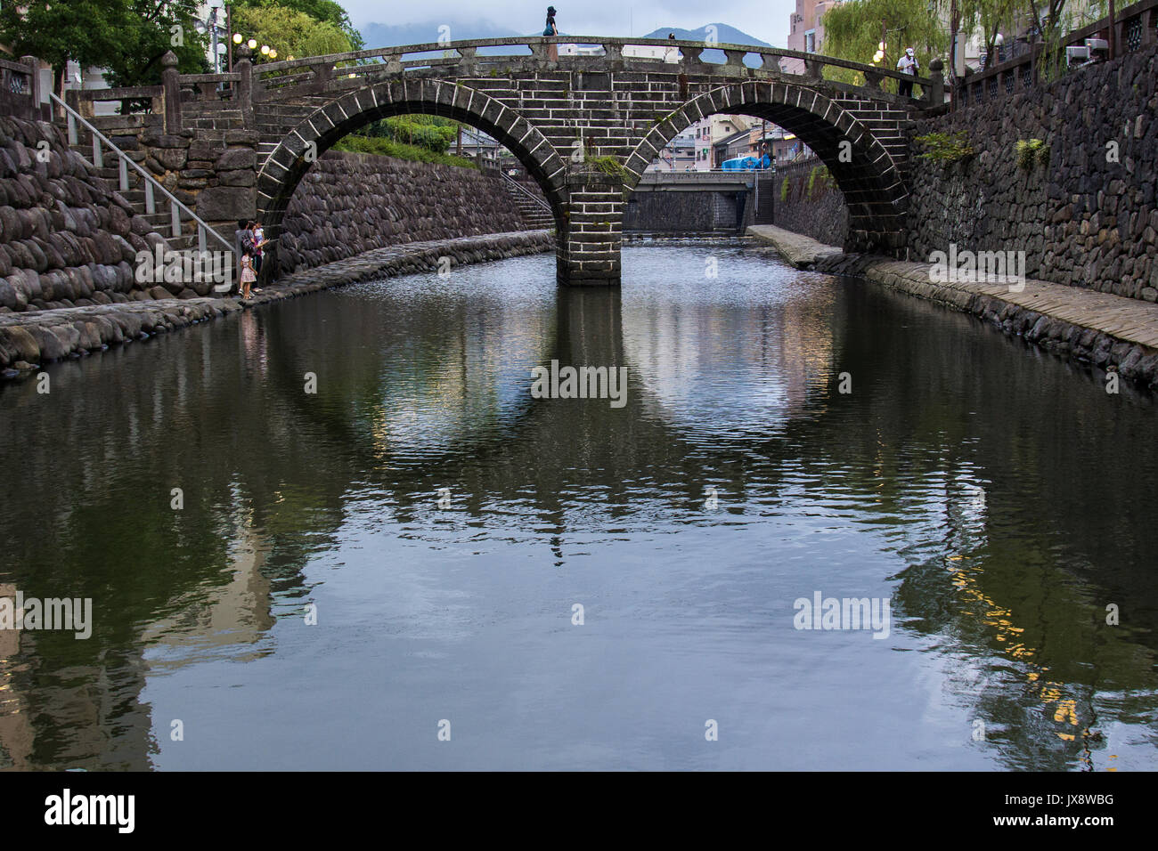 Meganebashi or Spectacles Bridge, over the Nakashima River was built in Nagasaki in 1634.  Said to be the oldest stone arch bridge in Japan and has be - Stock Image