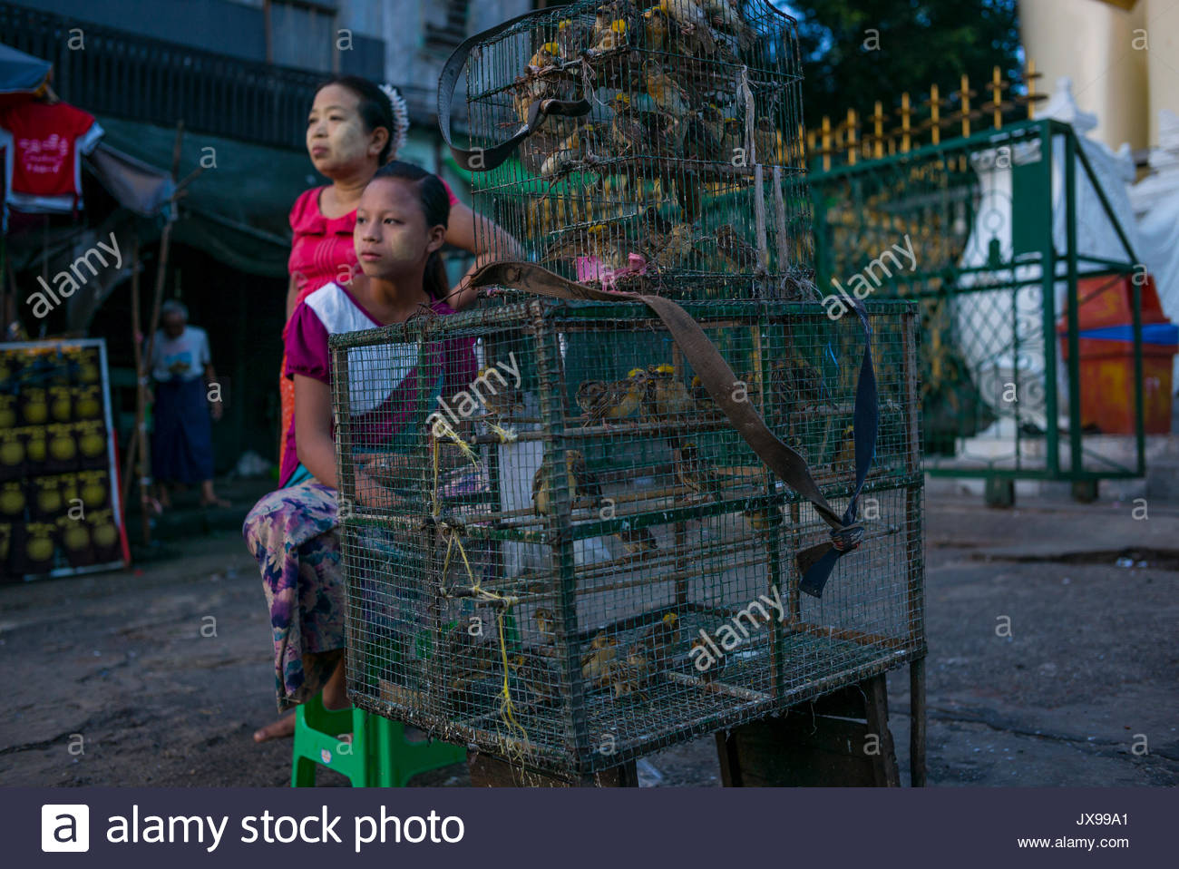Street vendors sit beside a cage of birds they are selling. - Stock Image