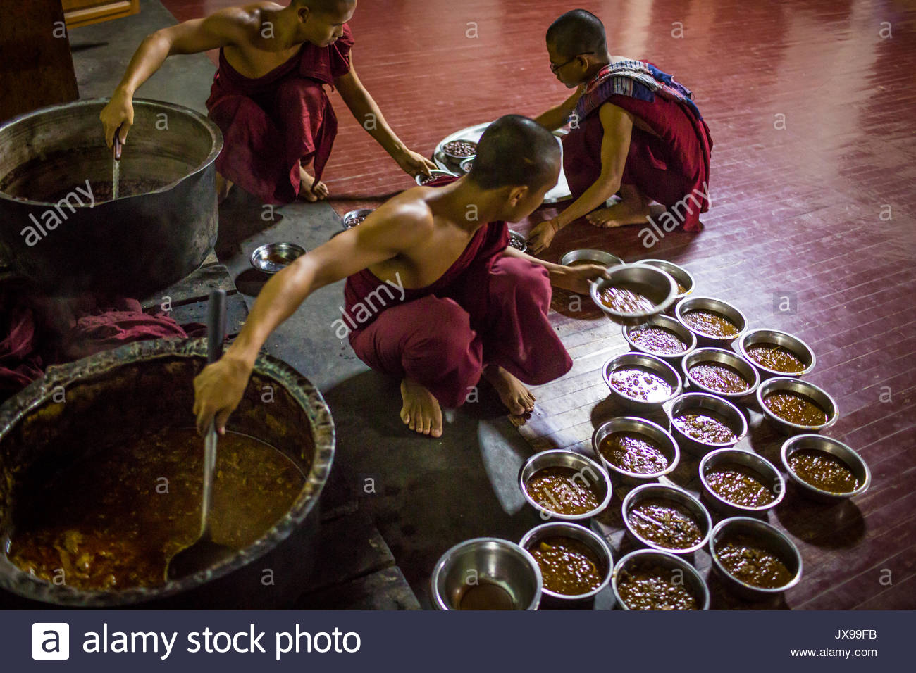 Two young monks place small bowls of food onto a tray for a third monk to deliver. - Stock Image