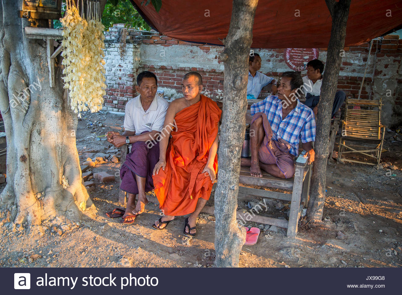 A monk sits on a bench next to two other men. - Stock Image