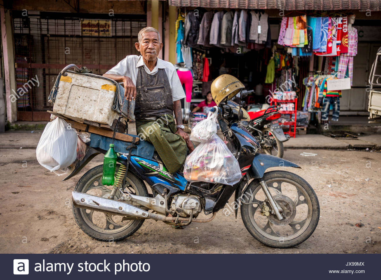 A man sits on a motorcycle filled with goods at the Mytchina street market. - Stock Image