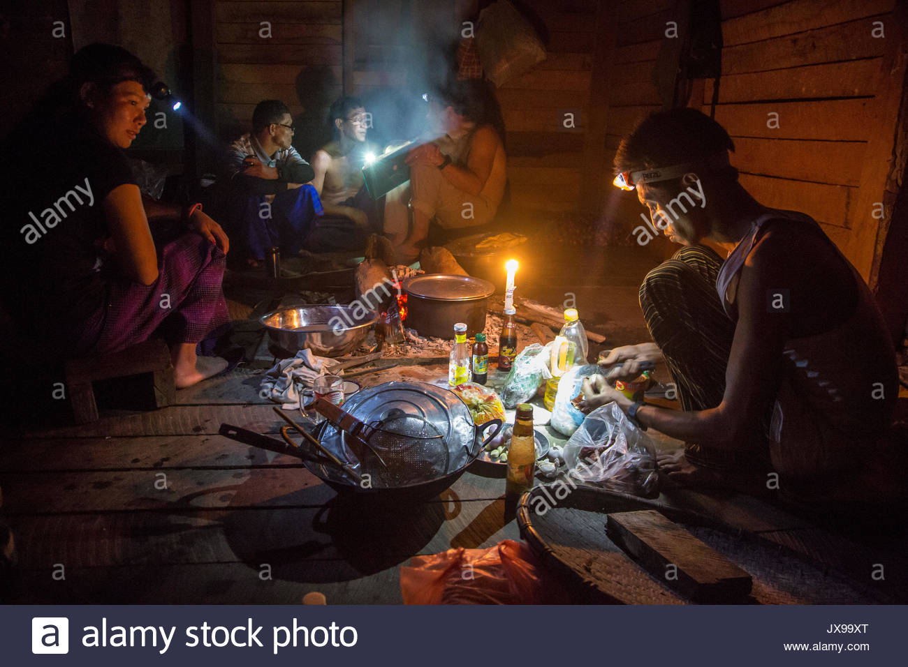 Porters prepare a meal by lamplight in a darkened cabin. - Stock Image