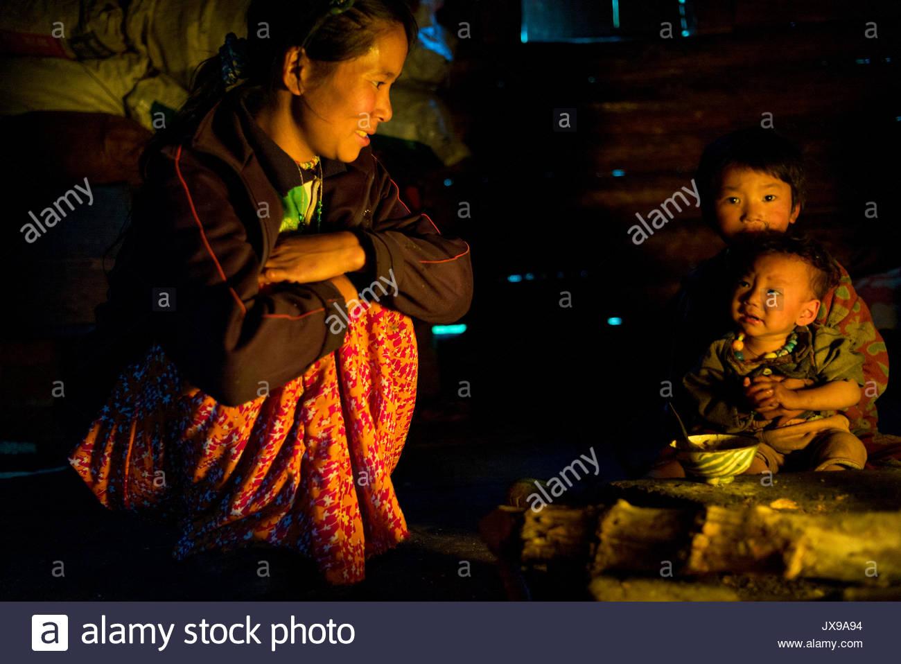 Buddhist villagers huddle around a fire. - Stock Image