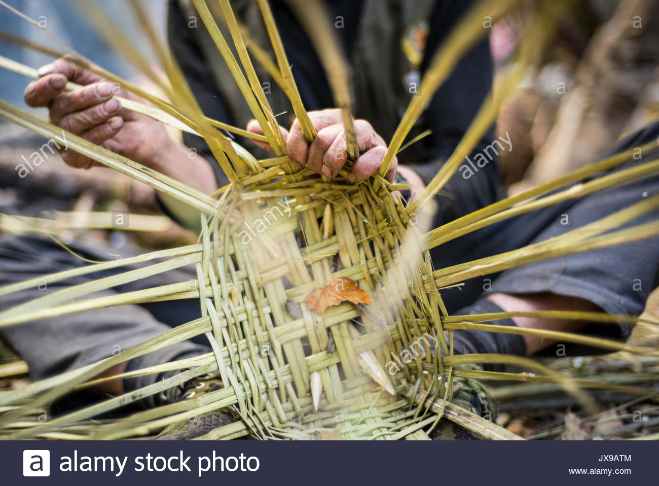 A person weaving a basket out of reeds and grasses. - Stock Image