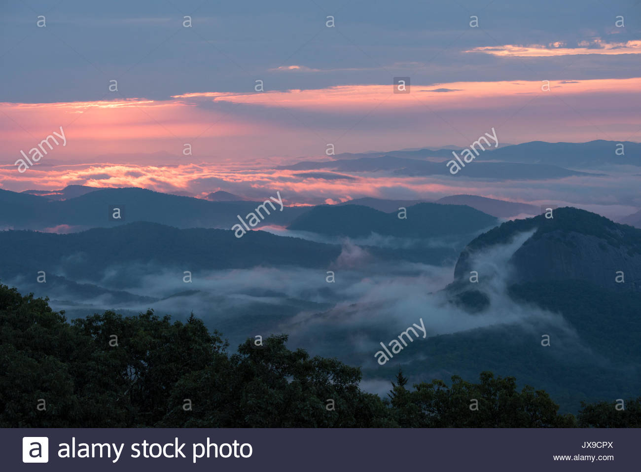 Sunrise looking towards Looking Glass Rock from the Looking Glass Overlook on the Blue Ridge Parkway in the Pisgah National Forest. - Stock Image